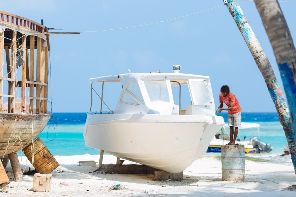 man working on boat on the beach